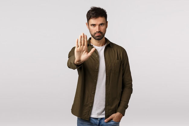 Time to stop. concerned asking quit, warn someone, prevent making same mistake. serious-looking assertive and confident young man pulling stop gesture, extend arm in forbid sign