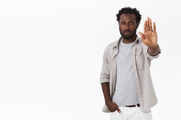 È ora di fermarsi a pensare. uomo barbuto afroamericano dall'aspetto serio con gesto di arresto