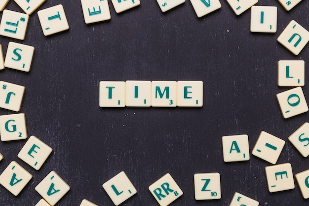 Time text on scrabble letters on black backdrop