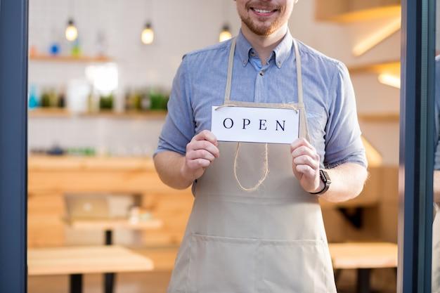 열릴 시간입니다. 유리 문 뒤에 서서 카페가 열려 있음을 보여주는 동안 라벨 태그를 들고 쾌활한 긍정적 인 젊은이