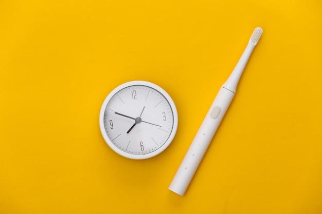 歯を磨く時間。黄色い歯ブラシと時計