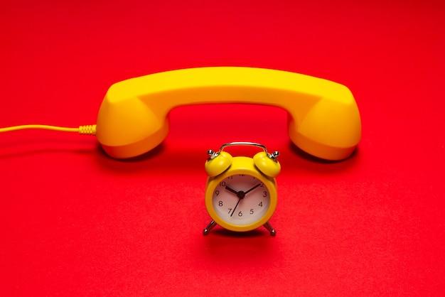 Время звонить. желтая трубка и будильник на красном фоне. скопируйте пространство.
