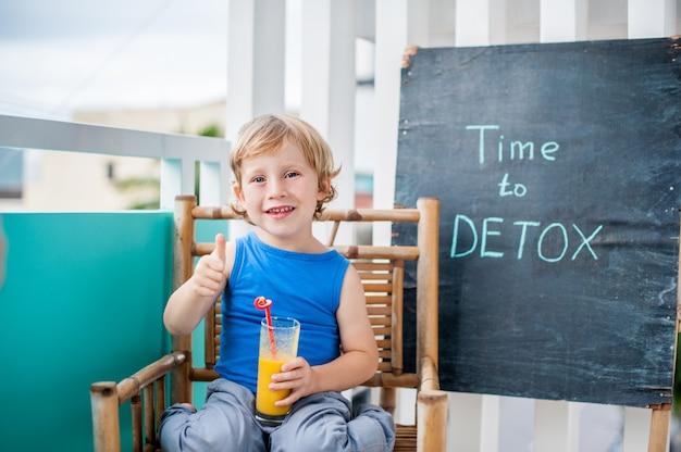 Время для детокса меловой надписью. мальчик пьет свежий, полезный для здоровья напиток из фруктов. фруктовый коктейль, сок, молочный коктейль. концепция здоровья