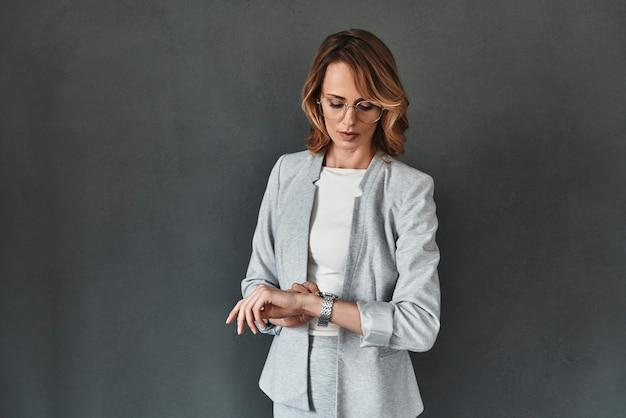 ビジネスをする時間。灰色の背景に立って時間をチェックするスマートカジュアルウェアの思いやりのある若い女性