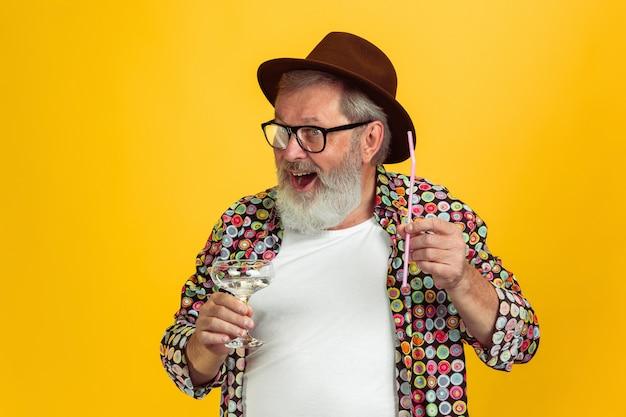 飲む時間。黄色のスタジオの背景に分離されたアイウェアのシニアヒップスターの男の肖像画。技術と楽しい高齢者のライフスタイルのコンセプト。トレンディな色、永遠に若さ。広告のコピースペース。