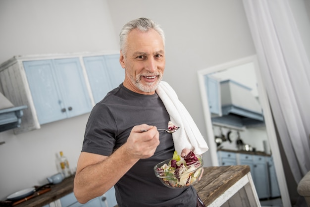 食事の時間。キッチンに立って、カメラを見ながら左手にボウルを持っている魅力的な年金受給者