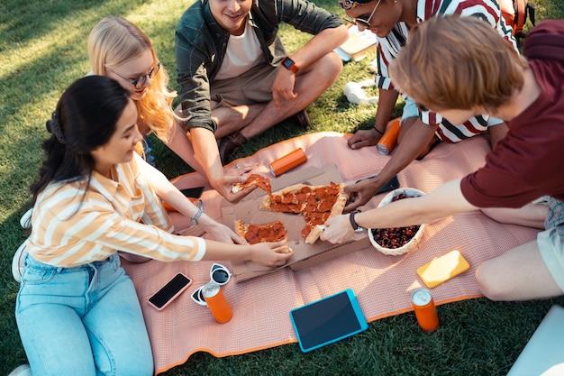 Время поесть. улыбающиеся друзья сидят на лужайке, делят пиццу и обсуждают свои будущие экзамены.