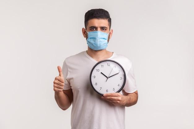 コロナウイルスと戦う時が来ました。時計を保持している衛生的なマスクの男、新しいウイルスの流行の警告