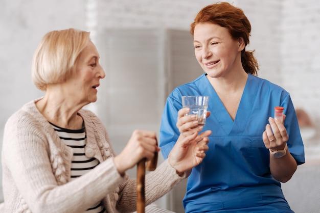 Пора выздоравливать. веселая, целеустремленная умелая женщина дает своему пациенту стакан воды для приема таблеток, заботясь о здоровье старушек