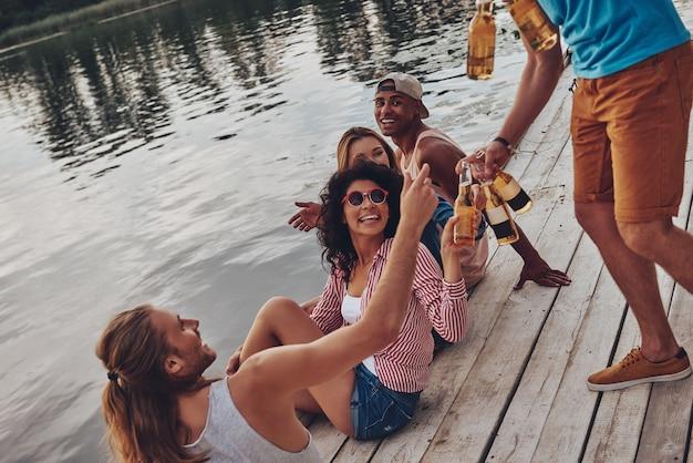 リフレッシュする時間です。桟橋に座って笑顔でビールを飲みながらカジュアルな服装で幸せな若者のグループ