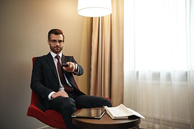 Пора отдыхать. бизнесмен, выбирая канал по телевизору на красном стуле в гостиничном номере. цифровой планшет и газета за столом