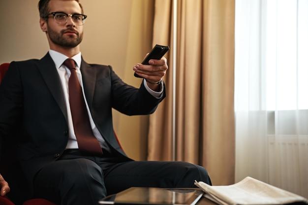 Пора отдыхать. крупный план бизнесмена, выбирающего chanel по телевизору на красном стуле в гостиничном номере. цифровой планшет и газета за столом
