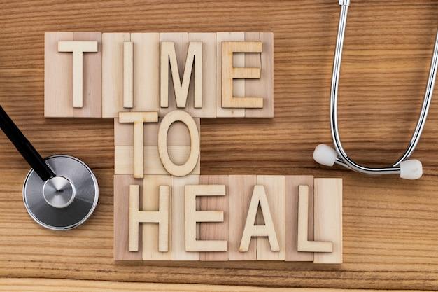 Время исцелять текст старинными буквами на деревянных блоках со стетоскопом. концепция медицины.