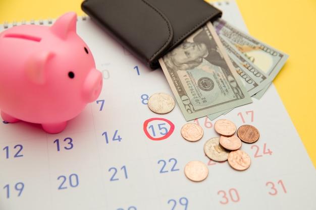 投資する時間、ビジネスコンセプト。ピンクの貯金箱とお金の紙幣、黄色の背景のカレンダーと財布。
