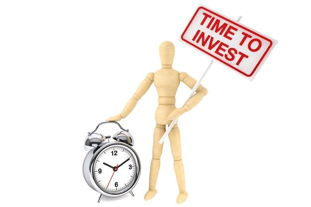 コンセプトを投資する時間。白い背景の上のバナーと目覚まし時計と木製のダミー