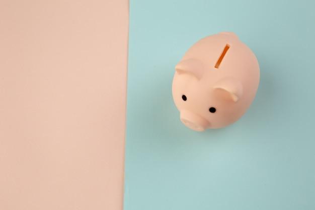投資する時間。ピンクブルーのパステルカラーの背景に貯金箱。
