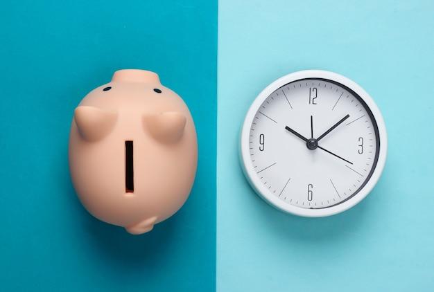 Время инвестировать. белые часы и копилка на синем фоне. минималистичный студийный снимок. вид сверху