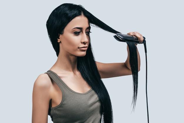Пора делать новую прическу! привлекательная молодая женщина в повседневной одежде укладывает длинные волосы щипцами для завивки, стоя на сером фоне