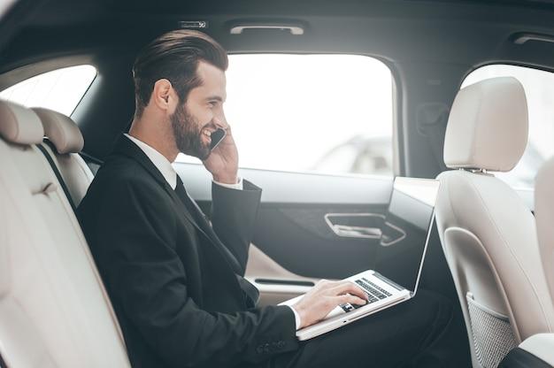 Время принимать решение. уверенный молодой бизнесмен работает на своем ноутбуке и разговаривает по телефону, сидя в машине