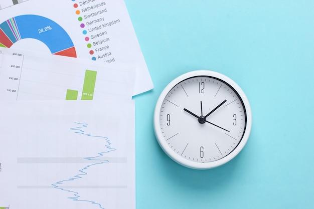 Время зарабатывать, вкладывать деньги. графики и диаграммы, часы на синем фоне. бизнес-концепция. вид сверху