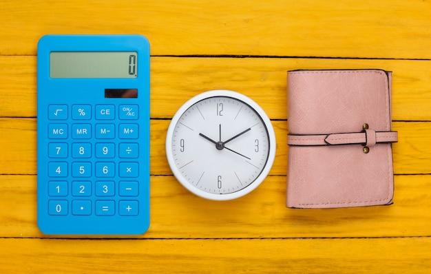 돈을 벌 시간. 흰색 시계와 지갑, 노란색 나무 표면에 계산기. 평면도