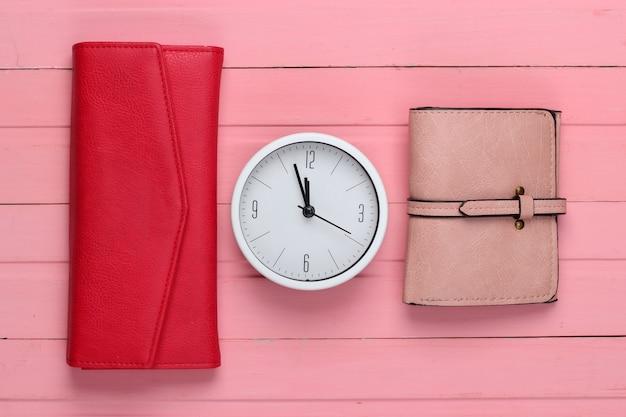 Время зарабатывать деньги. белые часы и бумажники на розовой деревянной поверхности. минималистичный студийный снимок. вид сверху