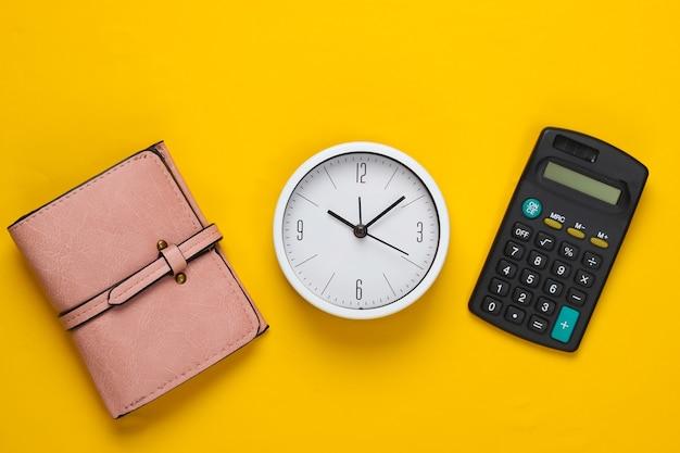 돈을 벌 시간. 노란색 배경에 흰색 시계, 계산기 및 지갑. 최소한의 스튜디오 촬영. 평면도