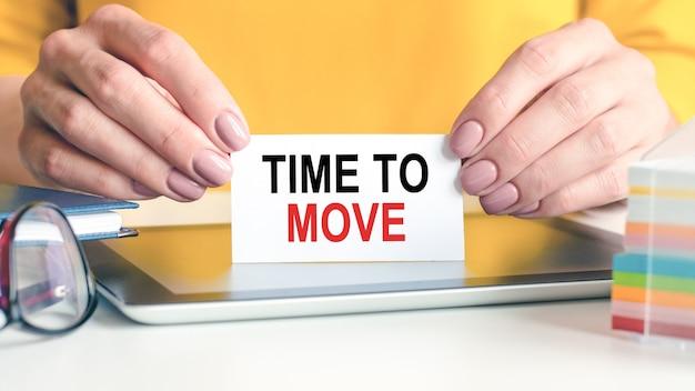Время двигаться написано на белой визитке в руках женщины. желтый фон. стаканы, планшет и блок с разноцветной бумагой для заметок. может использоваться для бизнеса, рекламной концепции.