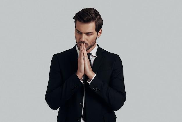 すべてを考え直す時間です。灰色の背景に立っている間、手を握りしめたままスーツを着たハンサムな若い男