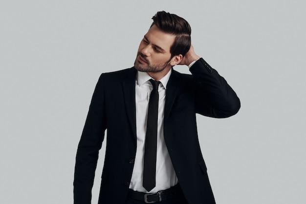 これを考え直す時が来ました。灰色の背景に立っている間笑顔のフルスーツのハンサムな若い男
