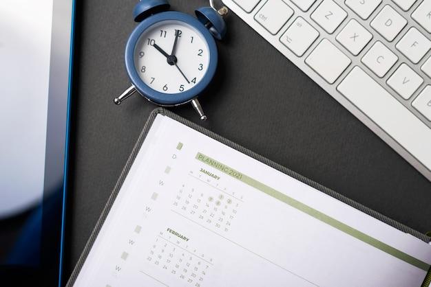 2021年を計画する時間、時計の議題とキーボードを備えたワークデスクの写真
