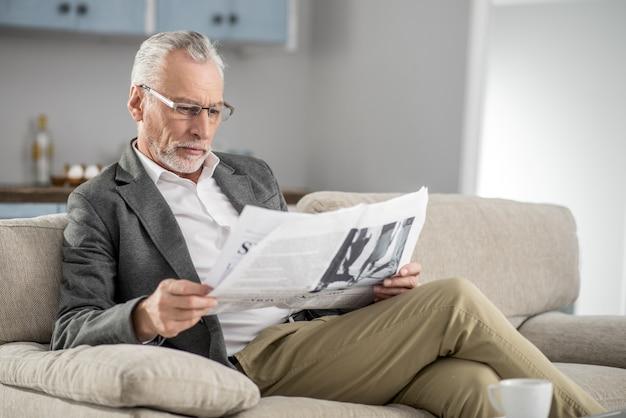 Время отдохнуть. сосредоточенный бородатый мужчина сжимает губы и склоняет голову, глядя на газету