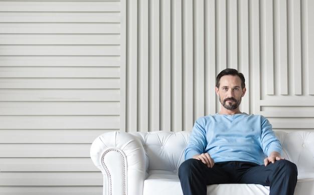 リラックスタイム。ソファに座って休憩しながら足に手を置く自信のある格好良い素敵な男