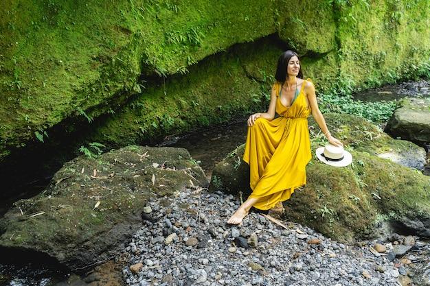 リラックスする時間。川の近くの流水を聞きながら積極性を表現するかわいい若い女性