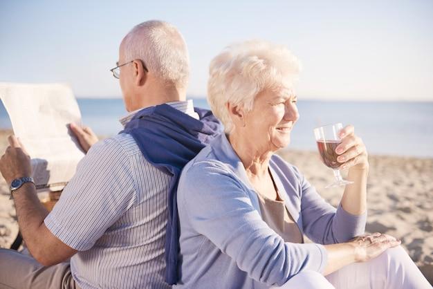 해변에서 휴식을 취할 시간입니다. 해변, 은퇴 및 여름 휴가 개념에서 수석 부부