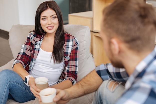 リラックスする時間。コーヒーを楽しみながら一緒に座って話し合う楽しい素敵な若い同僚