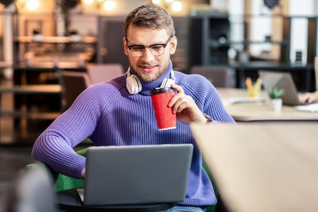 Время отдохнуть. довольный бородатый мужчина держит улыбку на лице, используя свой ноутбук