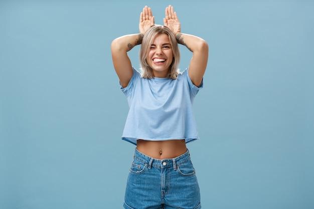 Время отдохнуть. портрет счастливой игривой милой блондинки в модной футболке с пирсингом на животе и татуировкой