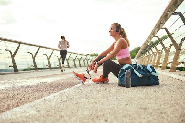 Время расслабиться, вид сбоку молодой красивой женщины в наушниках с прослушиванием протеза ноги