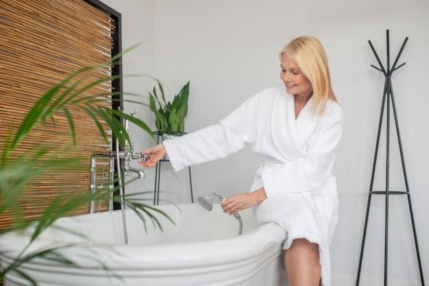 リラックスする時間。お風呂を計画している白いバスローブの女性