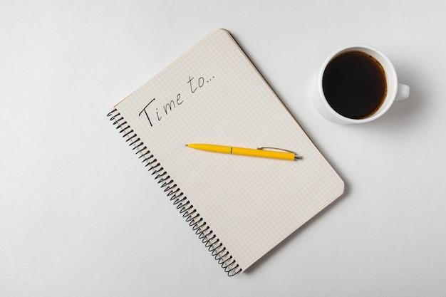 Время для напоминания. блокнот, ручка и чашка кофе на белой предпосылке.