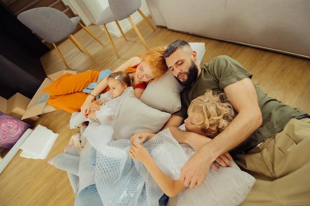 휴식 시간. 거실에서 함께 자는 동안 쿠션에 누워 있는 멋진 행복한 가족