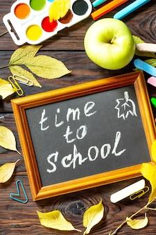 Время в школу обратно в школу концепции образование со школьными принадлежностями и яблоком