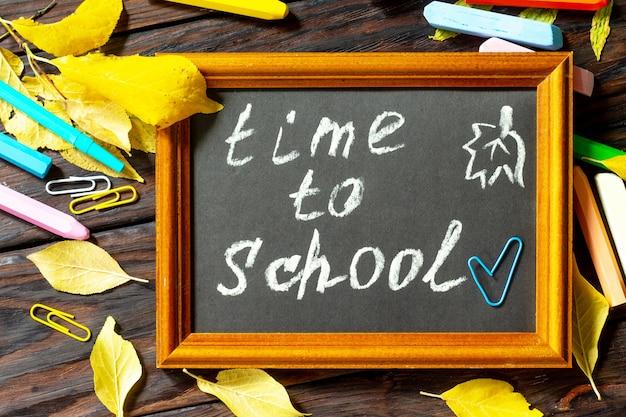 Время в школу снова в школу концепции образование со школьными принадлежностями вид сверху