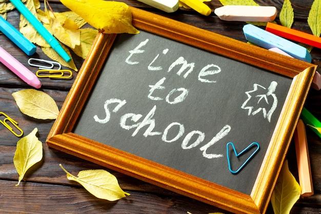 Время в школу снова в школу концепции образование со школьными принадлежностями