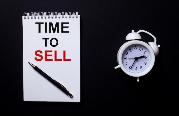 販売時間は、黒い表面の白い目覚まし時計の近くにある白いメモ帳に書かれています。