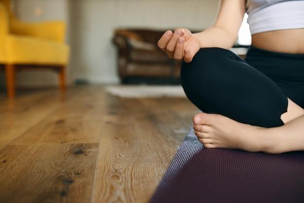 減速する時間。足を組んでマットの上に座って、ヨガ中に瞑想を練習している認識できない若い裸足の女性のトリミングされた画像。
