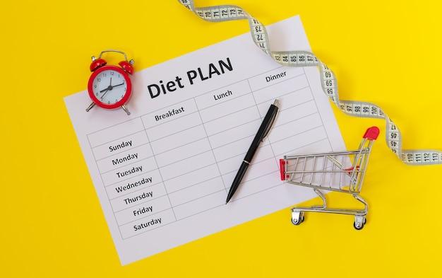 Пора начинать здоровое питание или диету для похудания. график диеты, часы, ручка, измерительная лента и вид сверху тележки
