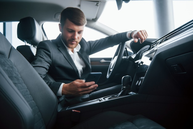 Пора остановиться и сделать перерыв. современный бизнесмен пробует свою новую машину в автомобильном салоне