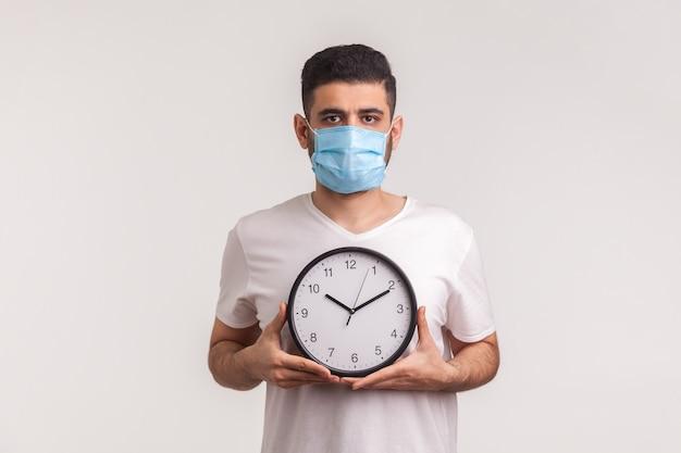コロナウイルスを止める時が来ました。時計を保持している保護マスクの男、新しいウイルスの流行の警告